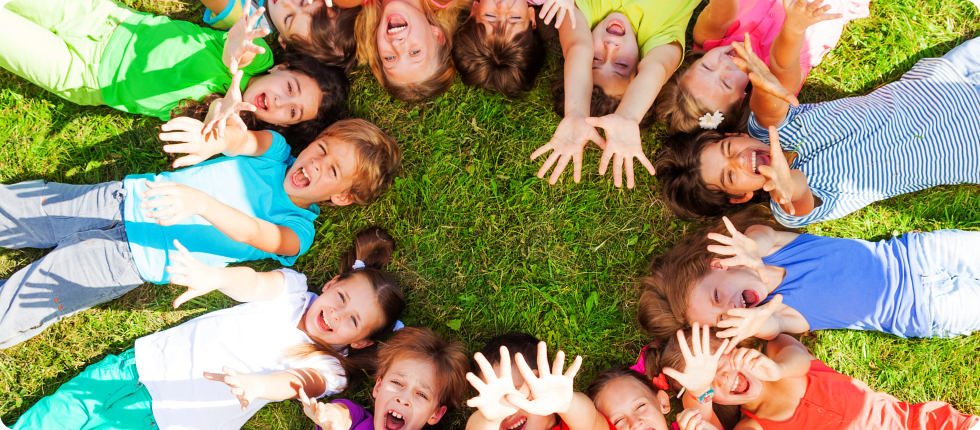 Children laying on the ground forming a circle