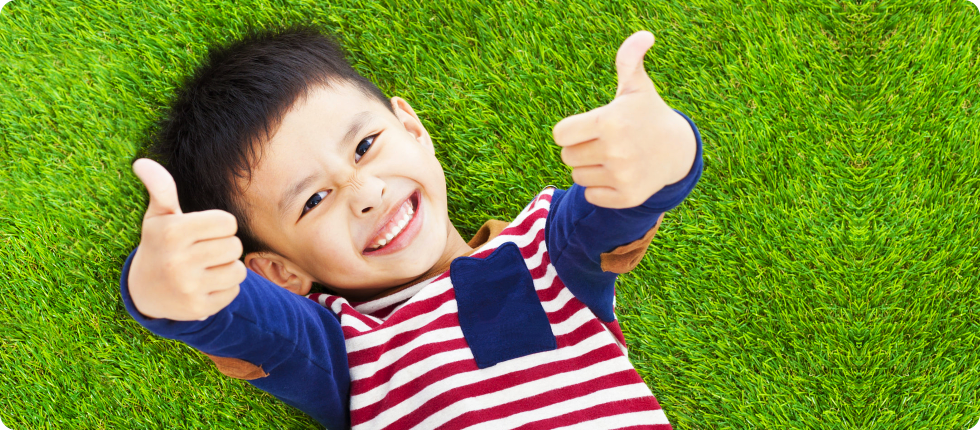 A boy laying on the ground and doing a thumbs up sign